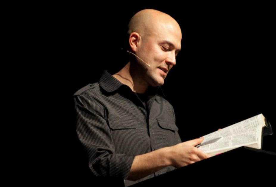 A young Joshua Harris reading from the Bible against a black backdrop